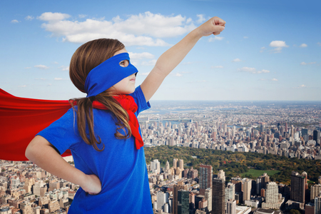 pretending: Masked girl pretending to be superhero against new york Stock Photo