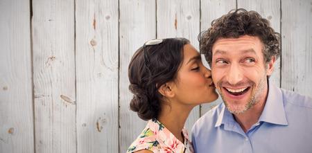 cheek: Pretty woman kissing man on cheek against wooden background Stock Photo