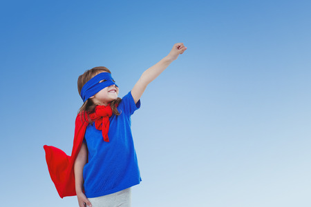 pretending: Masked girl pretending to be superhero against blue sky Stock Photo