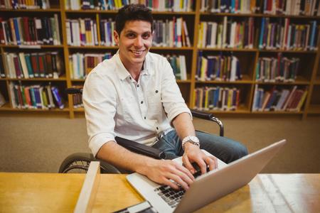 persona en silla de ruedas: Estudiante en la tipificación de la silla de ruedas en su computadora portátil en la biblioteca