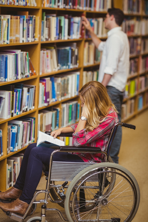 paraplegico: Student in wheelchair talking with classmate in library