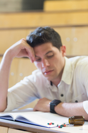 higher intelligence: Anxious male student during exam in lecture hall
