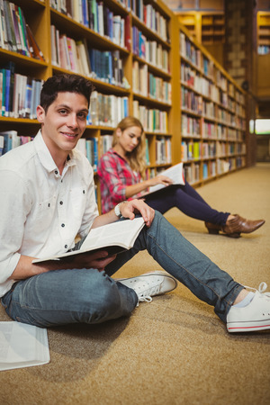 revising: Smiling male student revising on floor in library Stock Photo