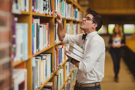 man studying: Nerd searching book while girl walking to him in library