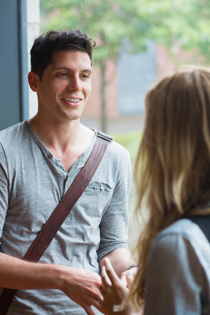 Smiling male student talking to a friend at the university