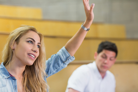 lecture: Attractive student raising hand during class at the lecture hall Stock Photo