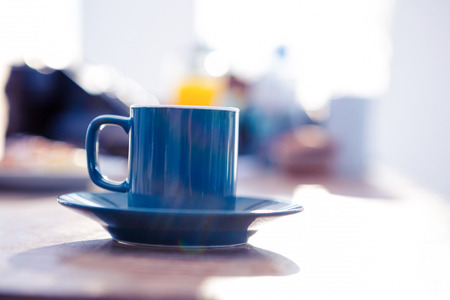 office life: Coffee cup on table in bright office Stock Photo