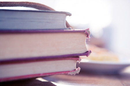 lit: Stack of books on table in brightly lit office Stock Photo