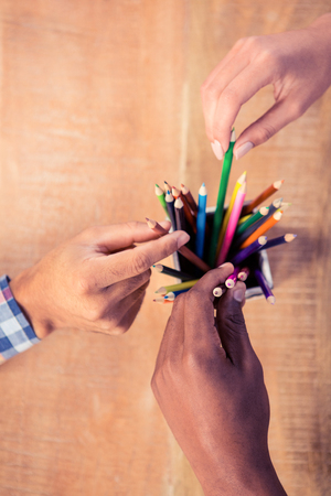 creatively: Business people choosing pencils from container in creative office