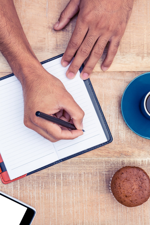 person writing: Cropped image of person writing on diary at table
