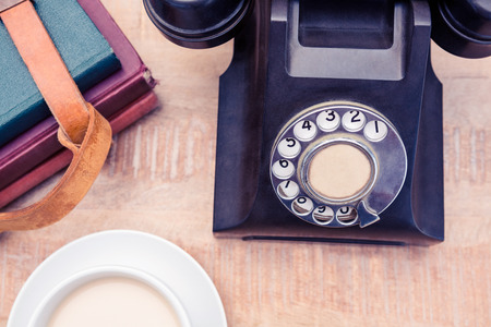 diaries: High angle view of old landline telephone with diaries and coffee on table