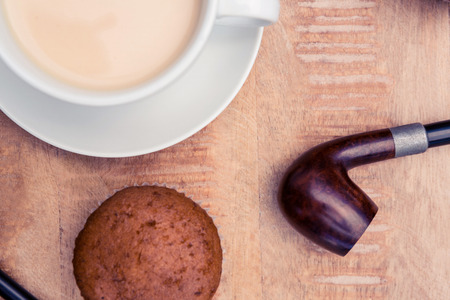 smoking pipe: Close-up of coffee with muffin and smoking pipe on table