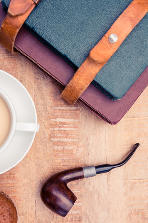 bad habit: Close-up of coffee with diaries and smoking pipe on table Stock Photo