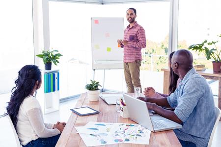 Vertrouwen zakenman geeft presentatie in creatieve kantoor