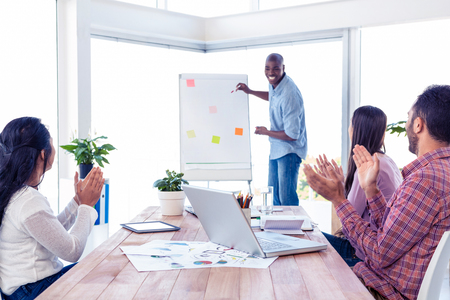applauding: Cheerful businessman giving presentation while team applauding in creative office Stock Photo