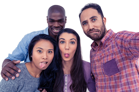 making face: Portrait of happy multi-ethnic friends making face against white background Stock Photo