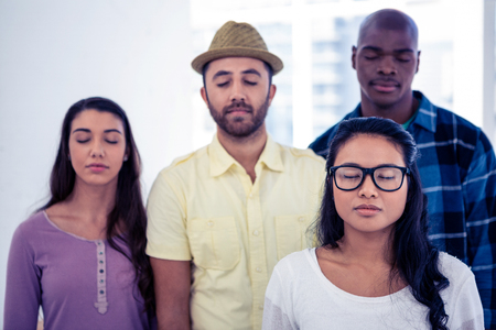 standing together: Businesswoman and team with eyes closed in creative office Stock Photo