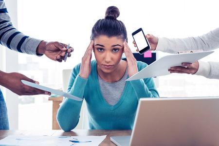 Portrait der gestressten Geschäftsfrau, die im kreativen Büro sitzt