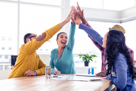 people in office: Cheerful business team doing high five while sitting in creative office