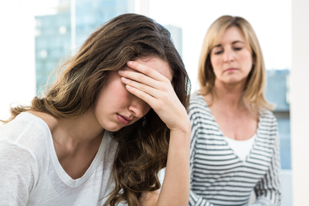 desolaci�n: Sad daughter against mother on sofa Foto de archivo
