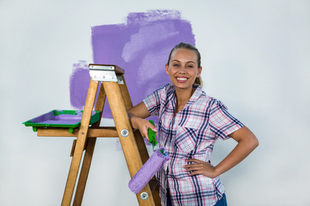 redecorating: Smiling woman painting a wall in new house