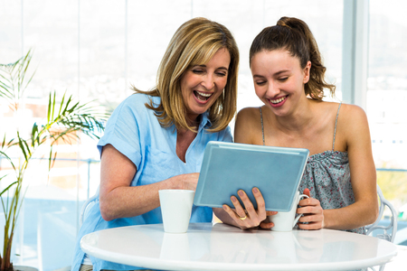 mom daughter: Mother and daughter watch tablet in the kitchen Stock Photo