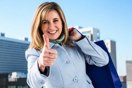 caritas felices: Mujer que hace un pulgar hacia arriba durante sus compras en la ciudad Foto de archivo