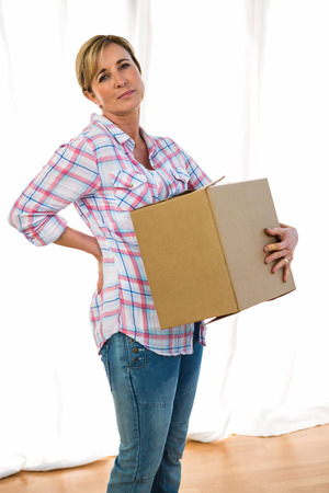 lower back pain: Woman holding a box feeling lower back pain Stock Photo