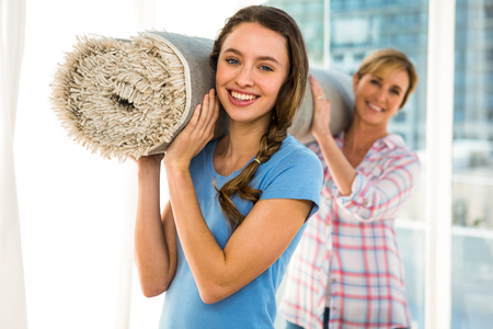 house moving: Mother and daughter holding a carpet together