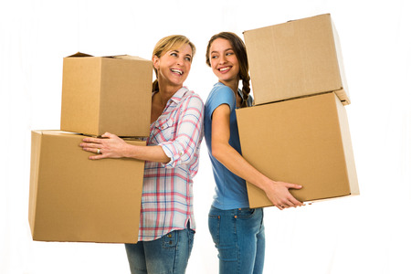 family moving house: Mother and daughter holding boxes and looking at each other Stock Photo
