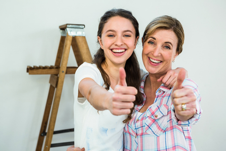 redecorating: Smiling mother and daughter with thumbs up redecorating Stock Photo
