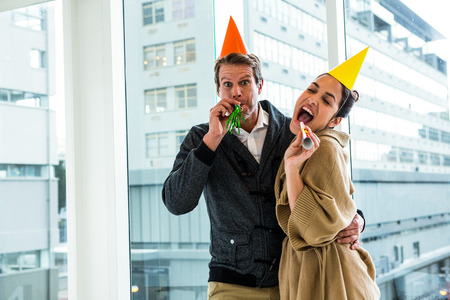 fun activity: Cheerful couple celebrating birthday against glass window at office