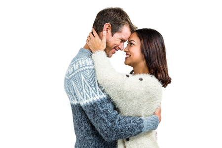 warm clothing: Couple wearing warm clothing embracing against white background