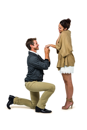 kneeling: Handsome man proposing beautiful woman while kneeling over white background Stock Photo