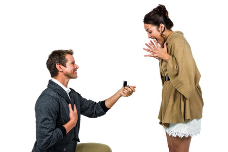 kneel down: Happy man offering engagement ring to partner against white background Stock Photo