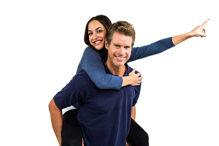 carrying girlfriend: Portrait of happy man carrying girlfriend on back against white background