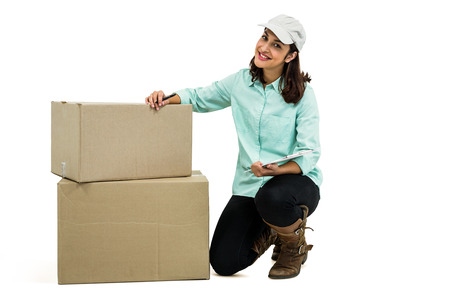 kneeling woman: Portrait of delivery woman with clipboard kneeling by box against white background Stock Photo