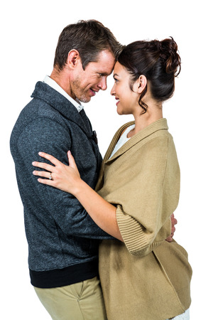 Side view of romantic couple hugging against white background