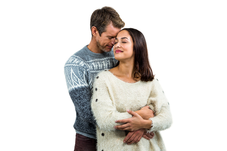 warm clothing: Romantic couple in warm clothing embracing against white background Stock Photo