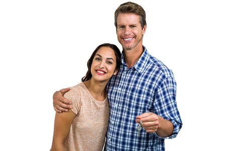 homeowners: Portrait of cheerful couple with keys standing against white background