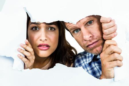 peeking: Portrait of fearful couple peeking through torn paper