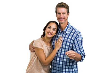 house moving: Portrait of cheerful couple holding home keys against white background