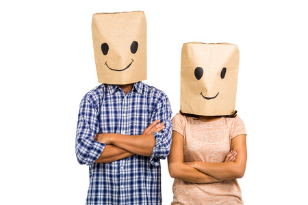 obscured face: Couple with arms crossed wearing smiley paper bags against white background