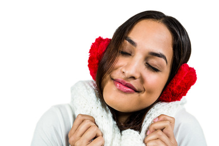 muff: Close-up of woman wearing ear muff while eyes closed against white background