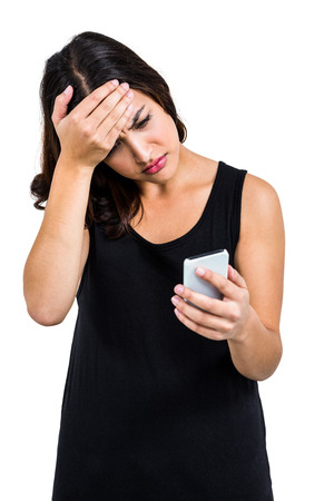 gloominess: Depressed woman holding phone while standing against white background