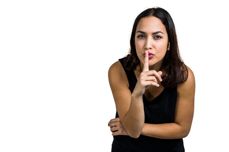 shushing: Portrait of woman with finger on lips against white background
