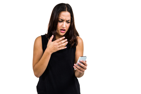 dreariness: Shocked woman using phone while standing against white background Stock Photo