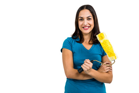 roller brush: Portrait of happy woman standing with paint roller brush