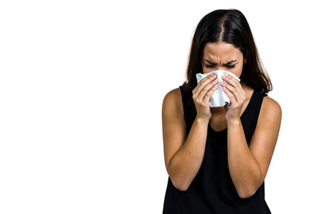 blowing nose: Unhappy woman blowing nose against white background Stock Photo