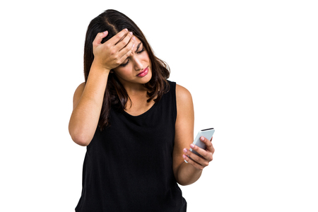 gloominess: Sad woman holding phone while standing against white background Stock Photo